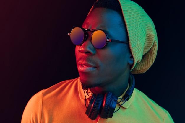 Młody Człowiek Hipster Słuchanie Muzyki W Słuchawkach W Czarnym Studio Z Neonów. Darmowe Zdjęcia