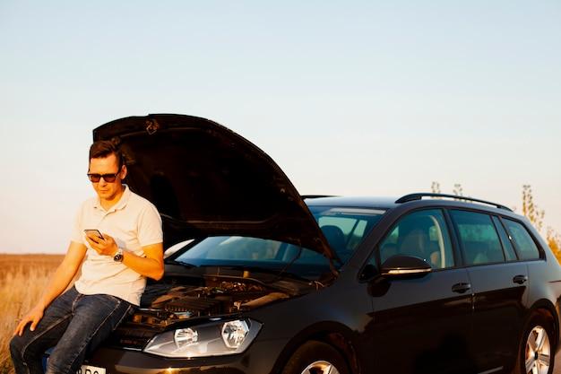 Młody człowiek i samochód z otwartą maską Darmowe Zdjęcia