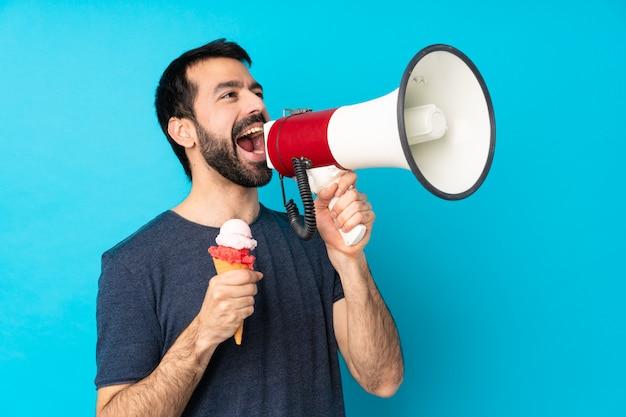 Młody Człowiek Krzyczy Przez Megafon Z Lody Kornetowymi Nad Odosobnioną Błękit ścianą Premium Zdjęcia