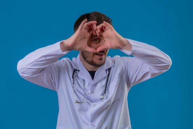 Młody Człowiek Lekarz Ubrany W Biały Fartuch I Stetoskop Robi Kształt Serca Z Ręką I Palcami Uśmiechnięty Patrząc Przez Znak Na Pojedyncze Niebieskie Tło Darmowe Zdjęcia