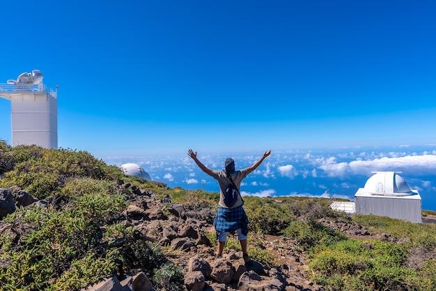 Młody Człowiek Na Szlaku Patrząc Przez Teleskopy Parku Narodowego Roque De Los Muchachos Na Szczycie Caldera De Taburiente, La Palma, Wyspy Kanaryjskie. Hiszpania Premium Zdjęcia