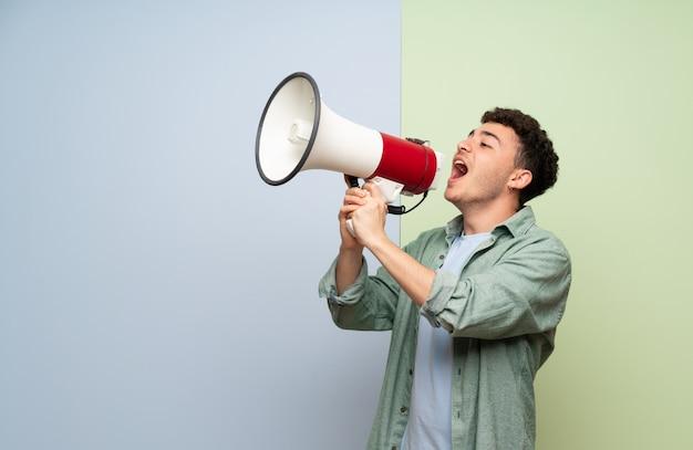 Młody Człowiek Nad Niebieskim I Zielonym Krzyczeć Przez Megafon Premium Zdjęcia