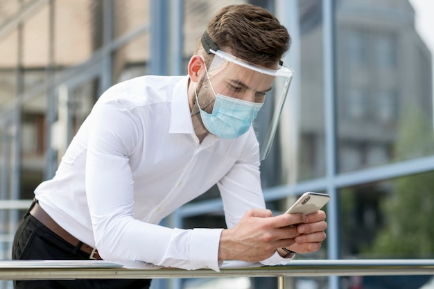 Młody Człowiek Odkryty Z Maską Sprawdzanie Telefonu Komórkowego Darmowe Zdjęcia