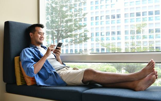 Młody człowiek opowiada na telefonie komórkowym podczas gdy siedzący na kanapie w domu Premium Zdjęcia