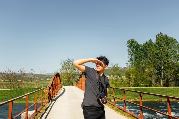 Młody Człowiek Osłania Oko Przed światłem Słonecznym Z Mienie Kamerą Darmowe Zdjęcia