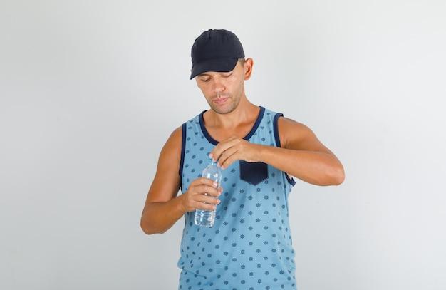 Młody Człowiek Otwierający Plastikowy Korek Butelki Wody W Niebieskim Podkoszulku Z Nakrętką Darmowe Zdjęcia