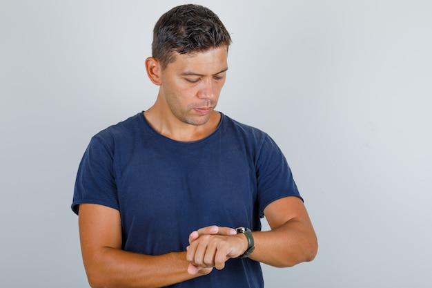 Młody Człowiek Patrząc Na Zegarek Na Nadgarstku W Granatowej Koszulce I Patrząc Punktualnie, Widok Z Przodu. Darmowe Zdjęcia