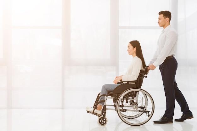 Młody człowiek pcha niepełnosprawnej kobiety na wózku inwalidzkim przeciw okno Darmowe Zdjęcia