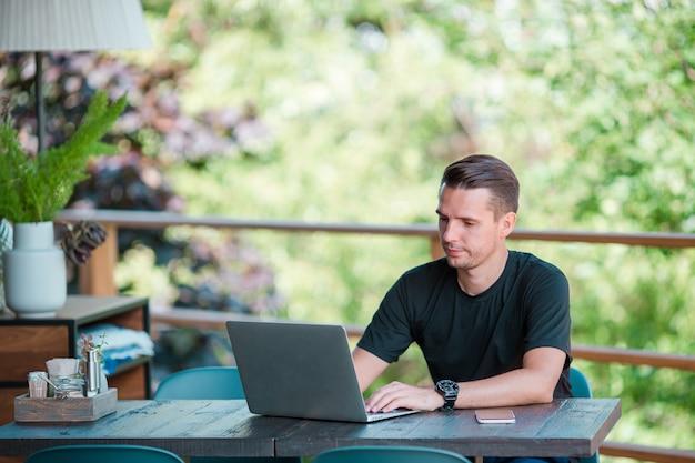 Młody człowiek pije kawę z laptopem w plenerowej kawiarni. człowiek za pomocą smartfona. Premium Zdjęcia