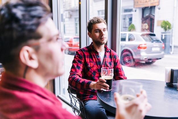 Młody Człowiek Pije Piwo Ze Swoim Przyjacielem W Restauracji Pub Darmowe Zdjęcia