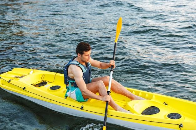 Młody Człowiek, Pływanie Kajakiem Po Jeziorze Premium Zdjęcia