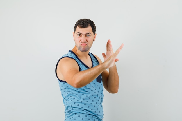 Młody Człowiek Pokazuje Gest Chop Karate W Niebieskim Podkoszulku I Wygląda Pewnie. Przedni Widok. Darmowe Zdjęcia