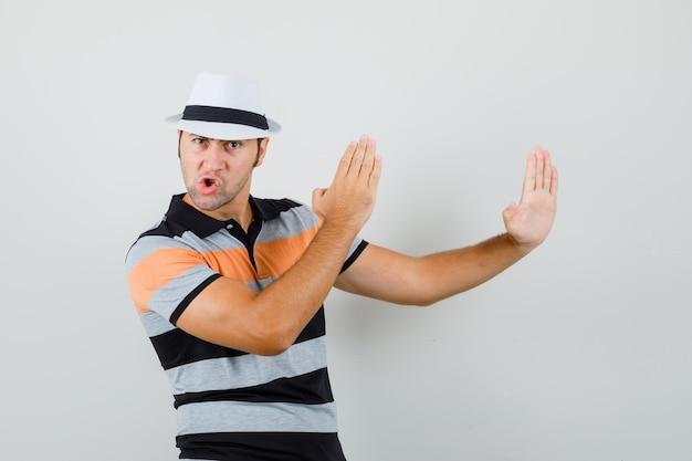 Młody Człowiek Pokazuje Kotlet Karate W Pasiastej Koszulce, Kapeluszu I Patrząc Elastyczny, Widok Z Przodu. Darmowe Zdjęcia