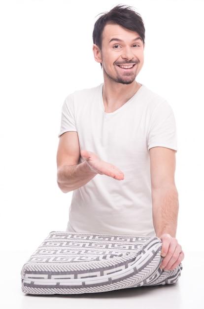 Młody Człowiek Pokazuje ładną Materac Na Bielu. Premium Zdjęcia