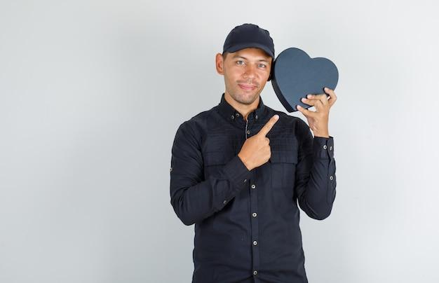 Młody Człowiek Pokazuje Pudełko W Czarnej Koszuli Z Czapką I Wygląda Wesoło Darmowe Zdjęcia