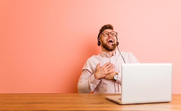 Młody Człowiek Pracujący W Call Center, śmiejąc Się, Trzymając Ręce Na Sercu, Pojęcie Szczęścia. Premium Zdjęcia