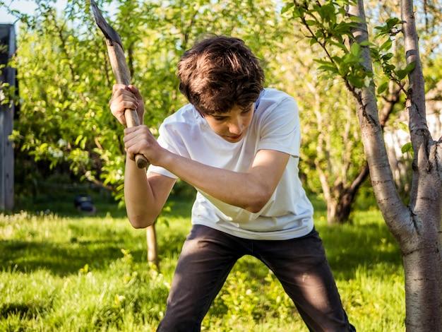 Młody Człowiek Pracuje W Ogródzie Z Cioską Blisko Drzewa Premium Zdjęcia