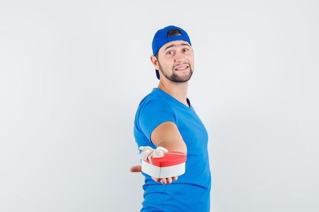 Młody Człowiek Prezentuje Pudełko W Niebieskiej Koszulce I Czapce I Wygląda Optymistycznie Darmowe Zdjęcia