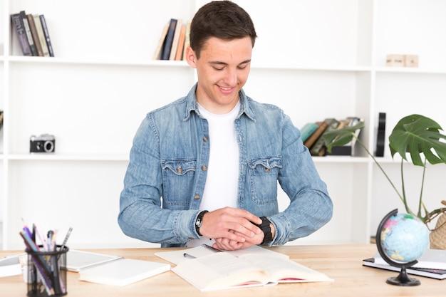 Młody Człowiek Przy Biurkiem Patrzeje Zegarek Darmowe Zdjęcia