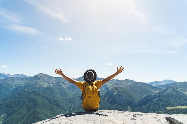 Młody Człowiek Ręce Do Góry Siedząc Na Szczycie Góry. Premium Zdjęcia