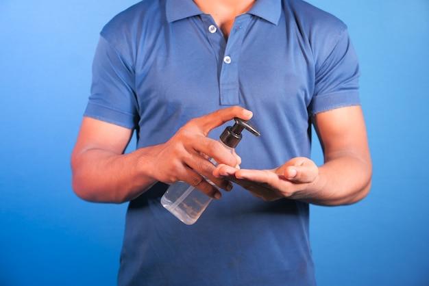Młody Człowiek Ręcznie Za Pomocą żelu Dezynfekującego Na Niebieskiej Przestrzeni. Premium Zdjęcia