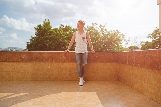 Młody Człowiek Relaksuje, Cieszy Się Słonecznego Dzień Podczas Gdy Stojący Na Bui Darmowe Zdjęcia