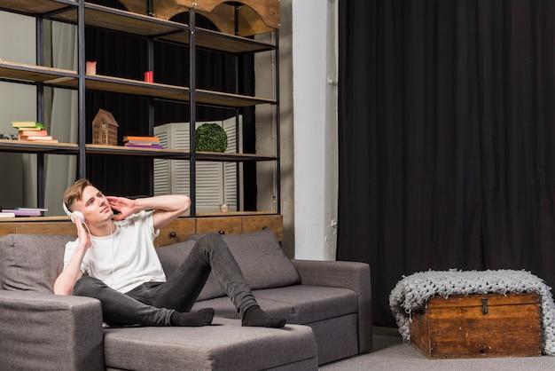 Młody człowiek relaksuje na kanapy słuchającej muzyce na hełmofonie w domu Darmowe Zdjęcia