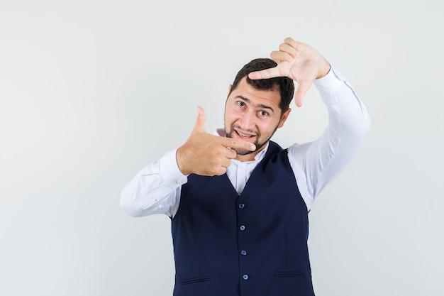 Młody Człowiek Robi Gest Ramy W Koszuli, Kamizelce I Wygląda Optymistycznie Darmowe Zdjęcia