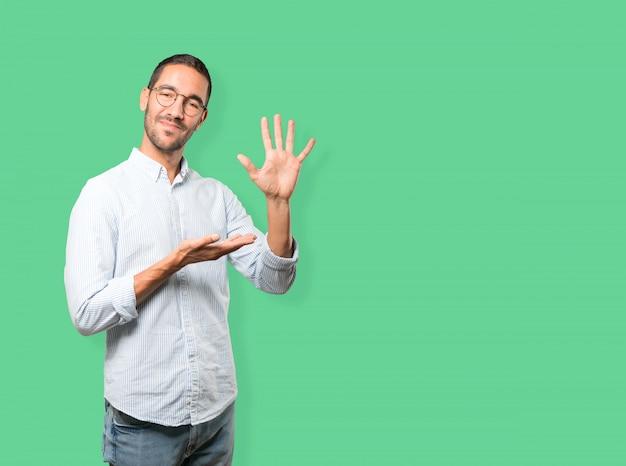 Młody człowiek robi gestowi numerowi pięć Premium Zdjęcia