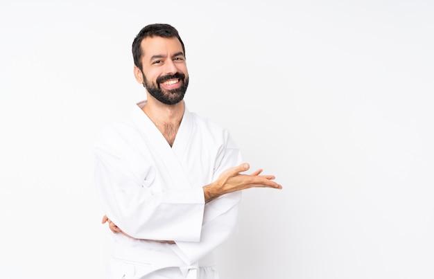 Młody człowiek robi karate nad bielem przedstawia pomysł podczas gdy patrzejący uśmiecha się w kierunku Premium Zdjęcia