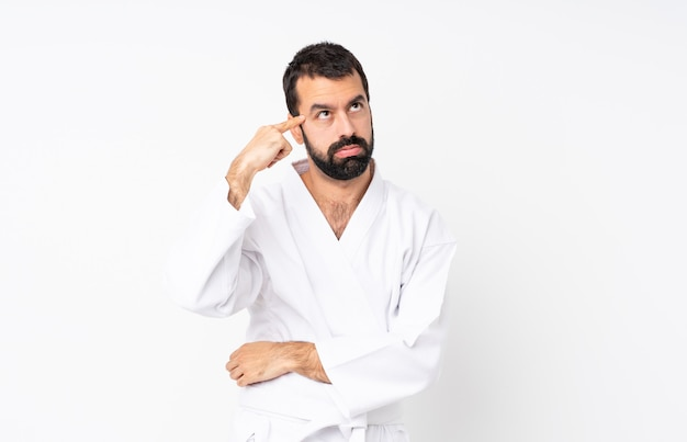 Młody człowiek robi karate nad odosobnionym bielem robi gestowi szaleństwa kładzenia palec na głowie Premium Zdjęcia