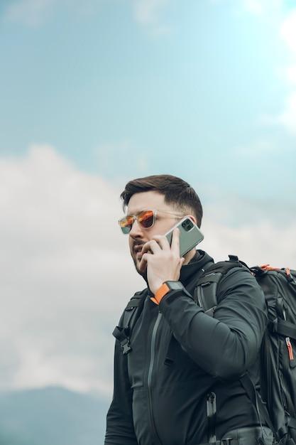 Młody Człowiek Robi Rozmowie Telefonicza Podczas Gdy Chodzi W Naturze Premium Zdjęcia