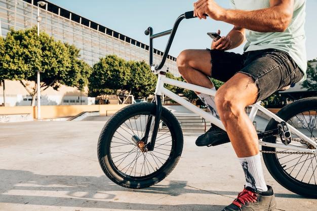 Młody człowiek rowerzysta trzyma jego telefon Darmowe Zdjęcia