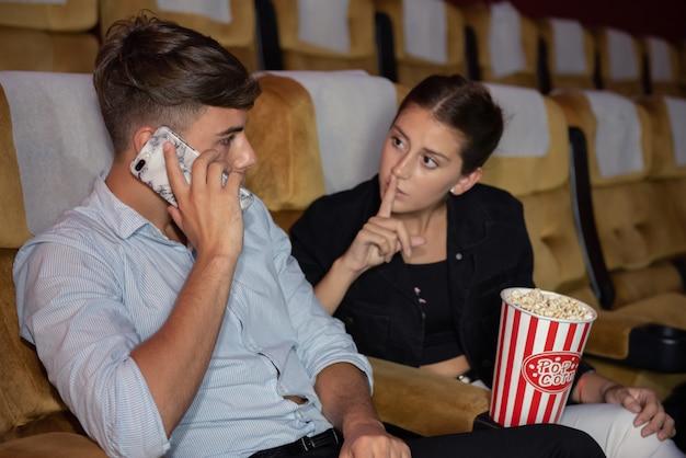 Młody Człowiek Rozmawia Przez Telefon Komórkowy Podczas Oglądania Filmu. Premium Zdjęcia