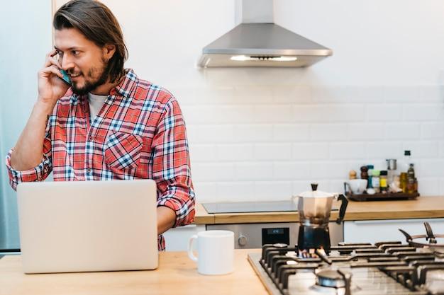 Młody człowiek rozmawia przez telefon komórkowy z laptopa i filiżanki kawy na blacie kuchennym Darmowe Zdjęcia