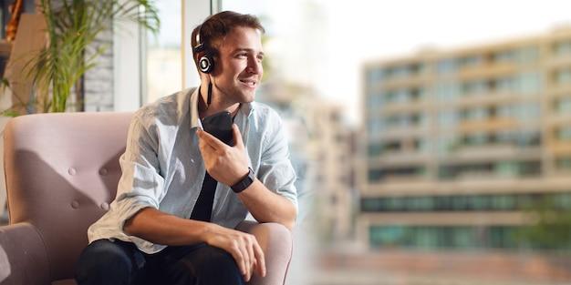 Młody Człowiek Siedzi I Mówi Bez Użycia Rąk I Uśmiecha Się Premium Zdjęcia
