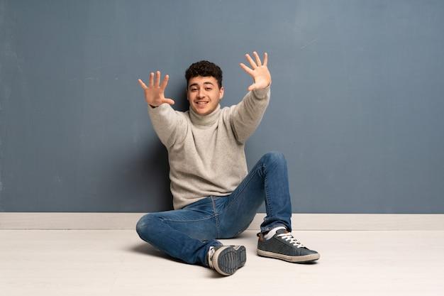 Młody Człowiek Siedzi Na Podłodze, Licząc Dziesięć Palcami Premium Zdjęcia