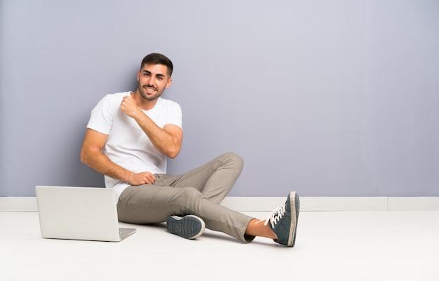 Młody człowiek siedzi na podłodze z laptopem świętuje zwycięstwo Premium Zdjęcia