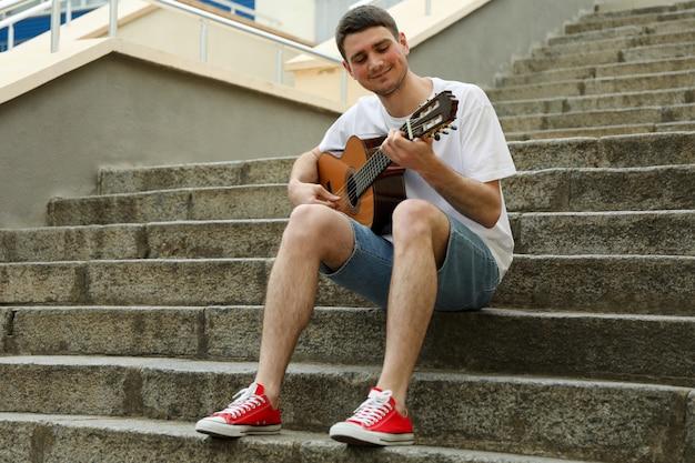Młody Człowiek Siedzi Na Schodach I Gra Na Gitarze Premium Zdjęcia