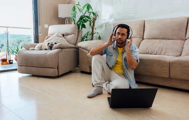 Młody Człowiek, Słuchanie Muzyki W Słuchawkach I Korzystanie Z Laptopa Do Pracy W Domu Darmowe Zdjęcia