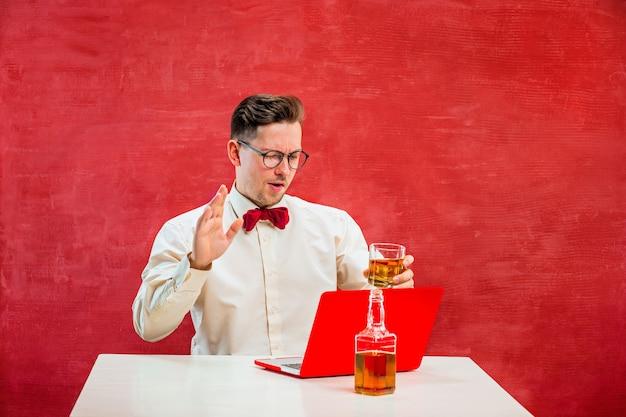 Młody Człowiek śmieszne Z Koniakiem Siedzi Z Laptopem W Walentynki Na Czerwonym Tle Studio. Koncepcja - Nieszczęśliwa Miłość Darmowe Zdjęcia