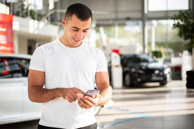 Młody Człowiek Sprawdza Jego Telefon Przy Przedstawicielstwem Handlowym Darmowe Zdjęcia