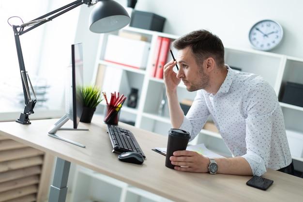 Młody Człowiek Stoi Przy Stole W Biurze, Trzyma Ołówek I Szklankę Kawy Premium Zdjęcia