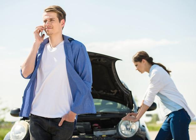 Młody człowiek stojący w pobliżu uszkodzonego samochodu i wzywając pomocy. Premium Zdjęcia