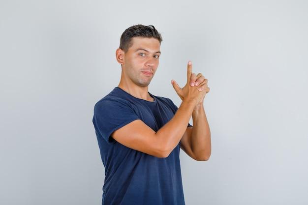 Młody Człowiek Strzelający Z Pistoletu Na Palec W Widoku Z Przodu Ciemnoniebieski T-shirt. Darmowe Zdjęcia