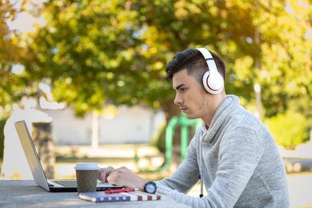 Młody Człowiek Studiuje Z Komputerem Podczas Słuchania Muzyki W Słuchawkach W Parku Bez Maski Premium Zdjęcia