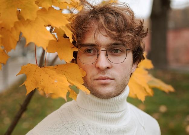 Młody Człowiek Stwarzających W Jesiennych Liściach Darmowe Zdjęcia
