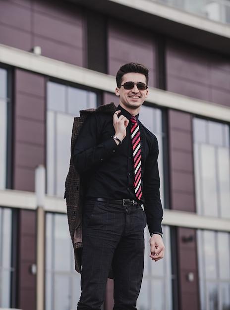 Młody Człowiek Sukcesu W Czarnej Koszuli I Płaszczu Uśmiecha Się, Stojąc Przed Biurem Premium Zdjęcia