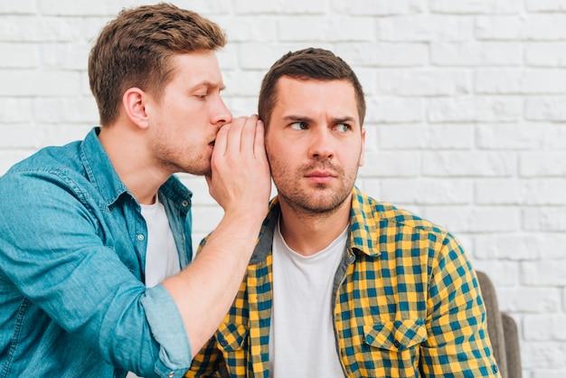 Młody człowiek szepcząc sekret w uchu przyjaciela Darmowe Zdjęcia