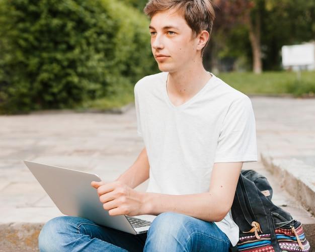 Młody Człowiek Trzyma Laptop W Parku Darmowe Zdjęcia